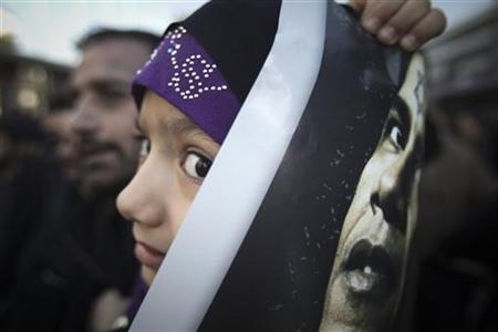 An Iranian girl carries an anti-U.S. placard bearing an image of U.S. President Barack Obama during a funeral for Iranian nuclear scientist Mostafa Ahmadi-Roshan, who was killed in a bomb blast in Tehran on January 11, in Tehran January 13, 2012. REUTERS/Morteza Nikoubazl