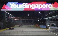 """Болид пилота """"Ред Булл"""" Себастьяна Феттеля на трассе в Сингапуре 25 сентября 2011 года. Крупнейший и наиболее популярный организатор автогонок в мире """"Формула 1"""" рассматривает возможность первичного размещения акций на рынке, сообщил Рейтер источник. REUTERS/Michael Caronna"""