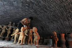 A worker moves clay statues out of a furnace in Dan Kwian village in Nakhon Ratchasima province, northeast of Bangkok March 13, 2012. REUTERS/Sukree Sukplang