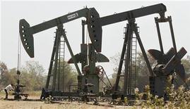 Рабочий проверяет вентиль на станке-качалке Oil and Natural Gas Corp (ONGC) в городе Ахмедабад, Индия 1 марта 2012 года. Цены на нефть повышаются после неожиданного сообщения о снижении запасов нефти в США. REUTERS/Amit Dave