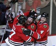 """Хоккеисты """"Чикаго"""" радуются победной шайбе, влетевшей в ворота """"Ванкувера"""" на игре в Чикаго, 21 марта 2012 года. """"Чикаго"""" и """"Ванкувер"""" выдали очередной напряженный матч в Западной конференции в среду - победа со счетом 2-1 в овертайме досталась игравшим дома """"ястребам"""". REUTERS/Jeff Haynes"""