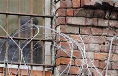 Охранник выглядывает из окна Бутырской тюрьмы в Москве 25 ноября 2011 года. Заключенный сбежал из колонии строго режима на севере России на арендованном его сообщниками вертолете. Через несколько часов приговоренного к 24 годам заключения убийцу поймали в сотне километров от колонии. REUTERS/Denis Sinyakov