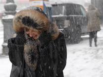 Девушка идет под снегом в Москве, 26 декабря 2011 года. Наступающие выходные в Москве будут мало похожи на весенние, несмотря на приближение апреля. REUTERS/Anton Golubev
