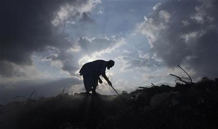 A man is silhouetted against the sun as he goes through a dumping ground for recyclable material in Karachi on September 1, 2011. REUTERS/Athar Hussain/Files