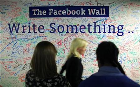 People walk past the Facebook wall inside their office in New York December 2, 2011. REUTERS/Eduardo Munoz/Files