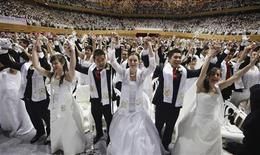 Newlyweds celebrate during a mass wedding ceremony of the Unification Church in Gapyeong, about 60 km (37 miles) northeast of Seoul March 24, 2012. The Unification Church founded by evangelist reverend Moon Sun-myung in Seoul in 1954, performed its first mass wedding in 1961 with 33 couples. Five thousand and two hundred couples attended the mass wedding on Saturday. REUTERS/Lee Jae-Won