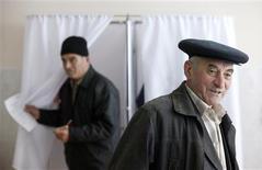 Люди голосуют на участке в Цхинвали 27 ноября 2011 года. Россия готовится взять реванш на повторных президентских выборах в отколовшейся от Грузии Южной Осетии, где прошлой осенью угодный Москве кандидат проиграл. Сейчас Москву устраивают оба лидера предвыборной гонки, но многие в мятежной республике не согласны с отменой результатов прошлых выборов и обещают продолжать борьбу. REUTERS/Eduard Korniyenko