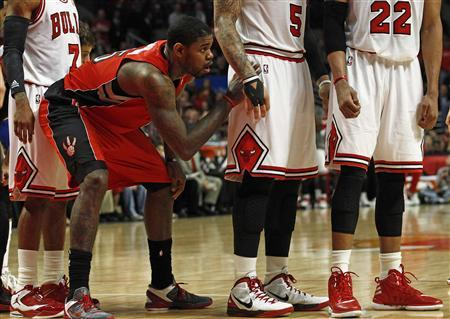 Toronto Raptors' Amir Johnson (2nd L) watches below Chicago Bulls' C.J. Watson (L), Carlos Boozer (2nd R) and Taj Gibson during their NBA basketball game in Chicago March 24, 2012. REUTERS/Jim Young