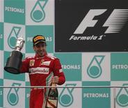 O piloto da Ferrari Alonso comemora no pódio após ganhar o GP da Malásia de Fórmula 1. Fernando Alonso obteve uma vitória dramática no Grande Prêmio da Malásia neste domingo, arrebatando o que seria o primeiro triunfo de Sérgio Pérez para a Sauber na categoria em uma corrida virada do avesso pelo clima. 25/03/2012    REUTERS/Tim Chong