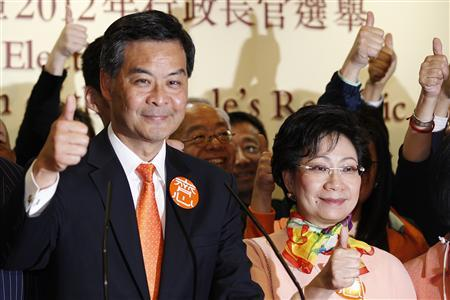 The next Hong Kong Chief Executive Leung Chun-ying celebrates with his wife Regina Tong Ching-yi as he attends a news conference after Leung won the chief executive election at a vote counting station in Hong Kong March 25, 2012. REUTERS/Tyrone Siu
