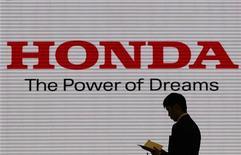 Человек стоит на фоне логотипа Honda Motor Co в автосалоне компании в Токио, 31 января 2012 г. Японский автостроитель Honda Motor Co в понедельник возобновил производство в Таиланде после почти полугодового перерыва, вызванного наводнением, сообщила компания. REUTERS/Toru Hanai
