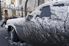 Женщина проходит мимо засыпанного снегом и грязью автомобиля в Москве, 9 февраля 2012 года. Рабочая неделя в Москве все еще не обещает весеннего тепла - от почти 10-градусных морозов по ночам столица сможет отдохнуть лишь к четвергу. REUTERS/Sergei Karpukhin