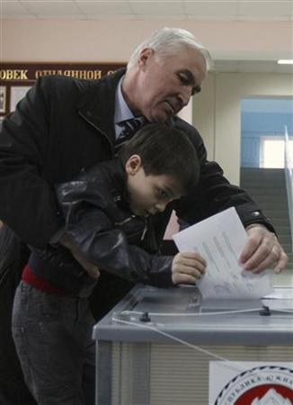 Presidential candidate Leonid Tibilov casts his vote with the help of a young relative at a polling station in Tskhinvali, in the breakaway region of South Ossetia March 25, 2012. REUTERS/Kazbek Basayev