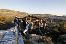 Jewish settlers carry wooden planks as they build a makeshift structure at the unauthorised outpost of Mitzpe Avihai, also known as Hill 18, near the settlement of Kiryat Arba outside the West Bank city of Hebron February 21, 2012. Israeli authorities demolished structures at the outpost several times in the past. REUTERS/Baz Ratner
