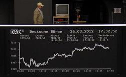 Мужчина идет по балкону над табло фондовой биржи во Франкфурте-на-Майне 26 марта 2012 года. Европейские рынки акций открылись повышением котировок после комментариев председателя ФРС США Бена Бернанке, указывающих на продолжение сверхмягкой политики центробанка. REUTERS/Remote/Amanda Andersen