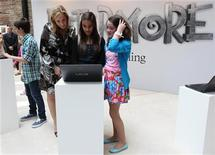 British author JK Rowling, creator of the Harry Potter series of books, poses with 12 year olds Kent children Ivy Aris (R) of Marden and Simran Sethi from Maidstone during the launch of new online website Pottermore in London June 23, 2011. REUTERS/Suzanne Plunkett
