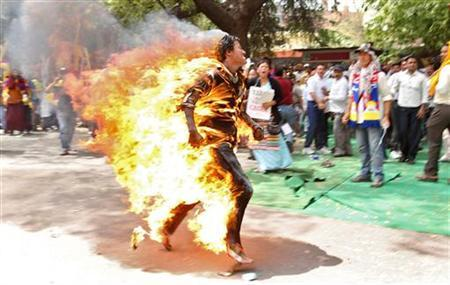 A Tibetan exile runs after setting himself on fire during a protest against the upcoming visit of Chinese President Hu Jintao to India in New Delhi March 26, 2012. REUTERS/Stringer