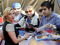 """Actress Kate Winslet signs autographs for fans as she arrives at the world premiere of """"Titanic 3D"""" at the Royal Albert Hall in London March 27, 2012. REUTERS/Paul Hackett"""
