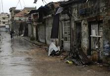 Мужчина проезжает на велосипеде мимо разрушенных зданий в Хомсе 28 марта 2012 года. Сирийские правительственные войска продолжили обстрелы и наступление на оплоты оппозиции в среду, несмотря на принятый во вторник президентом Башаром Асадом мирный план ООН, предусматривающий вывод войск из населенных пунктов, заявили активисты. REUTERS/Karam Karam