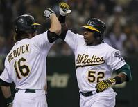 Oakland Athletics' Yoenis Cespedes (R) celebrates with teammate Josh Reddick after hitting a two-run homerun against Seattle Mariners' pitcher Shawn Kelley during the seventh inning of their second baseball game of the MLB American League season opening series in Tokyo March 29, 2012. REUTERS/Toru Hanai