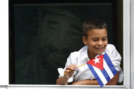 A Cuban boy with a portrait of Fidel Castro behind him watches Pope Benedict XVI's caravan make its way to the airport in Havana March 28, 2012. REUTERS/Jorge Silva