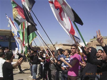Demonstrators holding Kurdish and Syrian opposition flags gather during a protest against Syria's President Bashar al-Assad in Qamishli March 23, 2012. REUTERS/Shaam News Network/Handout