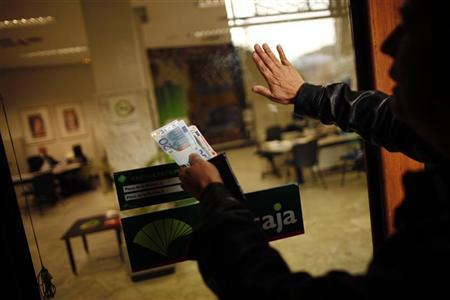 An union picketer holds euro notes as he tries to enter Unicaja bank to close it during a nationwide general strike in Malaga, southern Spain March 29, 2012. REUTERS/Jon Nazca