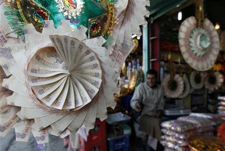 A Kashmiri shopkeeper sits near garlands made of currency notes at a market in Srinagar November 26, 2010. REUTERS/Fayaz Kabli/Files