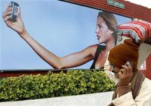 Индиец разговаривает по мобильному телефону перед рекламным постером в Нью-Дели, 20 января 2004 года. Российский диверсифицированный холдинг АФК Система хочет увеличить уставный капитал дочерней Sistema Shyam TeleServices Ltd (SSTL) вдвое до $2,4 миллиарда, но пока не определился с деталями. REUTERS/B Mathur
