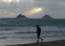 A man walks along Kailua beach as the sun rises over the Mokulua Islands, near where U.S. President Barack Obama is staying while he is on Christmas vacation in Hawaii, December 24, 2011. REUTERS/Hugh Gentry
