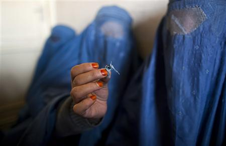 An Afghan woman holds up opium as she attends a counseling session at the Nejat drug rehabilitation centre, an organisation funded by the United Nations providing harm reduction and HIV-AIDS awareness, in Kabul January 29, 2012. With little funding and no access to substitution drugs such as methadone, treatment is rudimentary at Nejat for a problem that is growing in a dirt-poor country riven by conflicts for more than three decades. Opiate consumption in Afghanistan, where it has long been a medication but in recent years has been used increasingly for recreation, is also on a sharp rise. Nejat estimates around 60,000 women in Afghanistan regularly take illegal drugs, including hashish and marijuana. Shrouded in stigma, female drug users is a topic that is almost never mentioned in Afghanistan. Picture taken January 29, 2012. REUTERS-Ahmad Masood