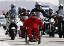 Macedonian paraplegic athlete Mile Stojkoski pushes himself on a highway, escorted by Serbian bikers, during a marathon from his native town of Krusevo to the London Olympics, in Belgrade March 28, 2012. REUTERS/Marko Djurica