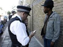 Полицейский изучает информацию в мобильном телефоне мужчины на улице Брикстона 14 августа 2008. Министерство внутренних дел Великобритании предприняло еще одну попытку получить доступ к телефонным звонкам, SMS и интернет-сообщениям любого жителя королевства, подготовив соответствующий законопроект. REUTERS/Andrew Winning