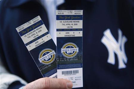 A New York Yankees fan shows his tickets to the first regular season MLB baseball game between the Yankees and the Cleveland Indians at the new Yankee Stadium in New York April 16, 2009. REUTERS/Eric Thayer