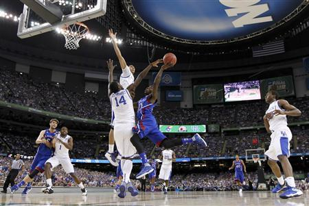 Kansas Jayhawks guard Tyshawn Taylor (10) drives to the net on Kentucky Wildcats forward Michael Kidd-Gilchrist (14) and forward Anthony Davis during the first half of their men's NCAA Final Four championship college basketball game in New Orleans, Louisiana, April 2, 2012. REUTERS/Lucy Nicholson