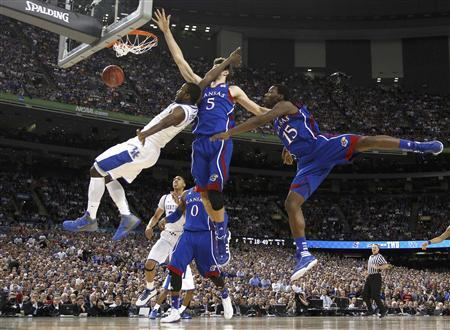 Kentucky Wildcats forward Michael Kidd-Gilchrist (L) falls while driving to the net on Kansas Jayhawks center Jeff Withey (5) and guard Elijah Johnson during the first half of their men's NCAA Final Four championship college basketball game in New Orleans, Louisiana, April 2, 2012. REUTERS/Jeff Haynes