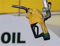 Заправочный пистолет в Сеуле, 27 июня 2011 года. Цены на нефть снижаются из-за предположений, что спрос в США сократится, а Саудовская Аравия сохранит добычу на высоком уровне.  REUTERS/Jo Yong-Hak