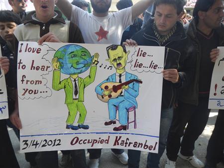Demonstrators hold up a sign during a protest against Syria's President Bashar Al-Assad in Kafranbel, near Idlib April 3, 2012. REUTERS/Raad Al Fares/Shaam News Network/Handout
