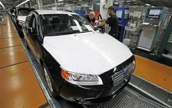 Workers make final adjustments to a new car at the main Volvo car assembly plant in Gothenburg, in this file picture taken May 20, 2010. REUTERS/Bob Strong/Files