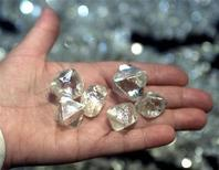 Мужчина держит алмазы весом более 50 карат в Якутии, 30 августа 2001 года. Российская алмазодобывающая госмонополия Алроса может выплатить дивиденды в размере 7,4 миллиарда рублей ($252 миллиона), или 25,2 процента чистой прибыли за 2011 год, сообщила компания в пятницу. REUTERS/Sergei Karpukhin