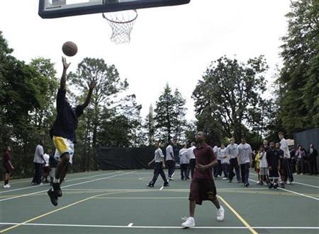 Players from the University of Connecticut men's basketball team hold a clinic for students from Eliot-Hine Middle School, based in Washington, on a basketball court on the grounds of the White House in Washington May 16, 2011. REUTERS/Yuri Gripas