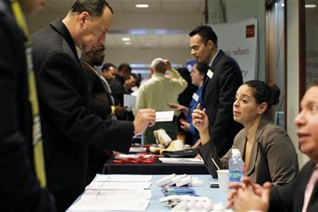 A man takes a business card during a military veterans hiring event in New York January 19, 2012. REUTERS/Brendan McDermid/Files