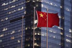 Флаг Китая развивается около бизнес-центра в Шанхае, 22 сентября 2011 года. Инфляция в Китае резко подскочила в марте в результате роста цен на продовольствие, удивив инвесторов, рассчитывавших на снижение ценового давления, которое дало бы Пекину пространство для смягчения монетарной политики. REUTERS/Carlos Barria