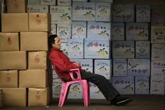 A vendor takes a nap near boxes of fruits at a wholesale market in Wuhan, Hubei province April 9, 2012. China's annual inflation rate hit 3.6 percent in March, with volatile food prices leading a temporary rebound that pushed costs above expectations but left intact the view that Beijing has the flexibility to ease monetary policy to support growth. REUTERS/Stringer (