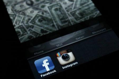 4月9日、米フェイスブックによる写真共有アプリ企業インスタグラムの防衛的買収は警戒を要する。写真はiPhoneのスクリーン上に表示されたフェイスブックとインスタグラムのアプリ(2012年 ロイター/Antonio Bronic)