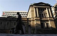 Мужчина проходит мимо здания Банка Японии в Токио 27 октября 2011 года. Банк Японии оставил во вторник монетарную политику без изменений, решив дождаться более тщательной оценки экономической ситуации, которая может указать на необходимость дальнейшего стимулирования для достижения целевого уровня инфляции в 1 процент. REUTERS/Yuriko Nakao