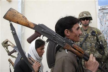 A U.S. soldier keeps watch as Taliban militants, part of a group of a hundred Afghan Talibans, hand over their weapons as they take part in the Afghan government's reconciliation and reintegration program in Laghman province March 12, 2012. REUTERS/ Parwiz/Files