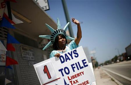 A woman dressed as the Statue of Liberty waves to attract people to a tax office in Miami April 14, 2008. REUTERS/Carlos Barria