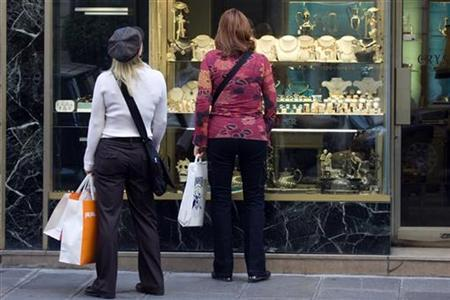 Women carry shopping bags as they look at a window display of jewellery shop in central Paris October 13, 2008. REUTERS/Charles Platiau