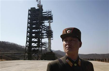 A soldier stands guard in front of the Unha-3 (Milky Way 3) rocket sitting on a launch pad at the West Sea Satellite Launch Site, during a guided media tour by North Korean authorities in the northwest of Pyongyang April 8, 2012. REUTERS/Bobby Yip